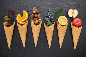 Fruit, nuts and chocolate with ice cream cones on a dark background