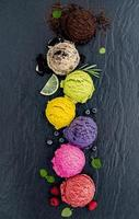 Colorful scoops of ice cream with fruit and herbs