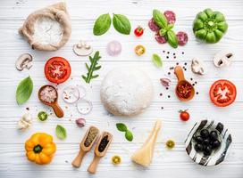 Fresh ingredients for pizza on shabby white wood
