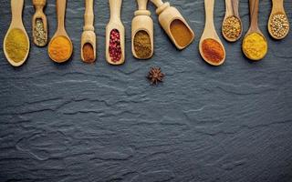 Various spices and herbs in wooden spoon on the black stone photo