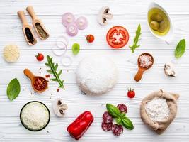 Pizza dough and ingredients on a shabby white background photo