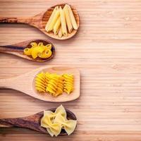 pasta surtida en cucharas de madera foto