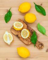 Lemons and lemon leaves on rustic wooden background