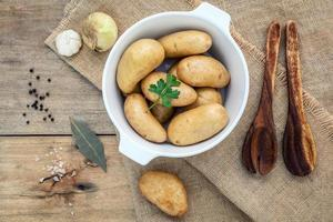 Fresh organic potatoes in a white ceramic bowl with herbs