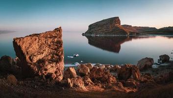 Large rocks at Lake Urmia with mountains and clear blue sky in Iran