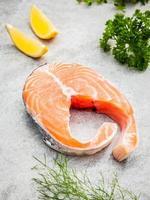 Fresh salmon fillet on stone background photo
