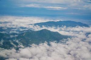 Aerial view of mountains and hills in clouds from airplane
