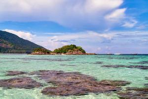 Rocks, water, mountains and cloudy blue sky at Koh Lipe island in Thailand
