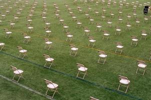 Rows of folding chairs on green lawn