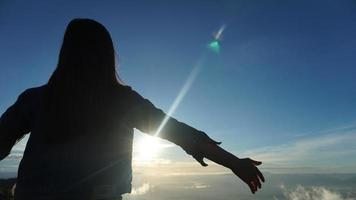 Woman with arms outstretched on top of a mountain with cloudy blue sky photo