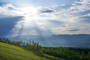 Iniciar sesión en una colina verde con montañas y cielo azul nublado foto