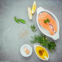 Salmon and fresh ingredients on a gray background photo