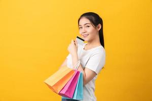 Woman holding multi colored shopping bags and credit card