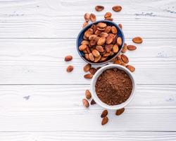 Cocoa powder and cacao beans on shabby white background