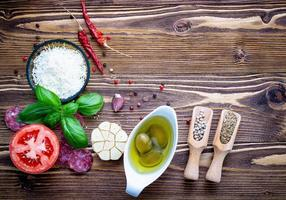 Fresh pizza ingredients on shabby wooden background photo