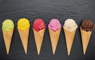 Colorful ice cream in cones on dark background