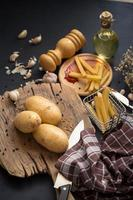 Potatoes on wooden board next to French fries on black table