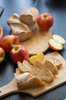 Whole and sliced apples with sliced baguette on wooden board on a dark wooden table