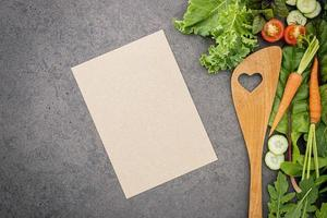 Menu mock-up with fresh salad and wooden spoon photo