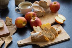 Whole and sliced apples with sliced baguette on wooden board with wooden utensils and a cup of coffee on a dark wooden table