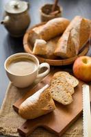 Manzanas enteras y en rodajas con baguette en rodajas sobre tabla de madera con una taza de café y un cuchillo de pan sobre una mesa de madera oscura.