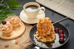 Waffles and cherries with honey, crispy almond tarts, cup of coffee, and a folded newspaper on black table