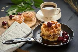 Waffles and cherries with honey in a pan, crispy almond tarts, and a cup of coffee on black table