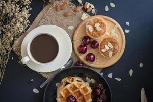 Waffles and cherries with honey, crispy almond tarts, and a cup of coffee on black table