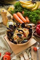 espaguetis y mejillones en un recipiente de madera sobre una tabla de madera junto a verduras