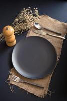 Top view of empty table setting of black plate, fork, knife, spoon, and pepper grinder on burlap on a black table photo