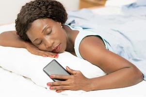 Bella mujer durmiendo en la cama con el teléfono en la mano foto
