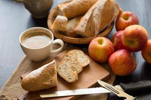 Whole apples with sliced baguette on wooden board with knives and cup of coffee on a dark wooden table