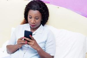 Young woman sitting in bed holding a cell phone