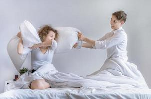 Couple has a pillow fight on the bed