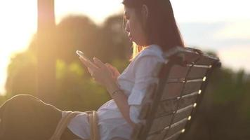 Woman Sitting on A Park Bench and Using a Smartphone