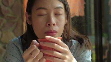 Closeup of an Asian Woman Drinking Tea in A Cafe