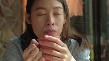 close de uma mulher asiática tomando chá em um café