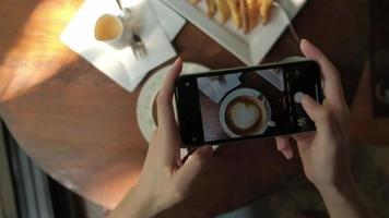 Closeup of A Woman Taking a Photo of Her Coffee