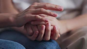 Two People Holding Hands for Encouragement. Close-up