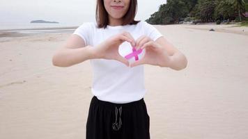 mulher fazendo formato de coração de sinal com a mão para câncer de mama.
