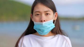 mulheres asiáticas mostram como colocar uma máscara protetora no rosto corretamente. maneira errada de usar uma máscara facial médica.