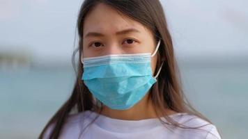 mulher asiática usando uma máscara facial fazendo gesto defensivo de fechar as mãos.