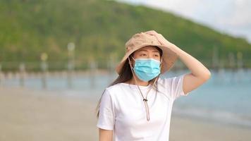 viajante de mulher asiática com máscara protetora, caminhando na praia. video