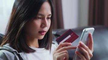 Frau, die mit einem Smartphone und einer Kreditkarte einkauft