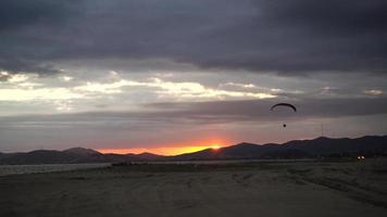 espectacular puesta de sol sobre una playa de arena con un parapente