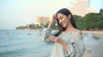 una mujer que usa su teléfono celular en la playa.