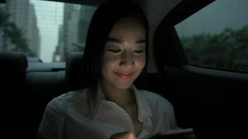 An Asian woman is using a phone while traveling on a taxi.