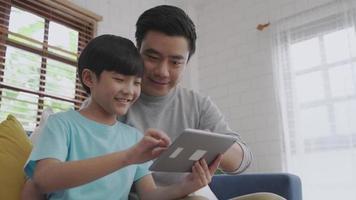 filho e pai pesquisando dados em um tablet na sala de estar