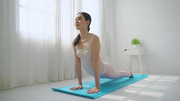 Asian woman practicing yoga at home video
