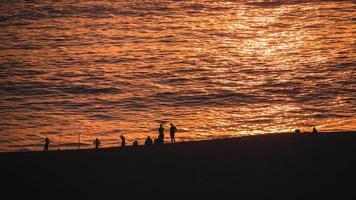 gente en la playa durante el atardecer foto